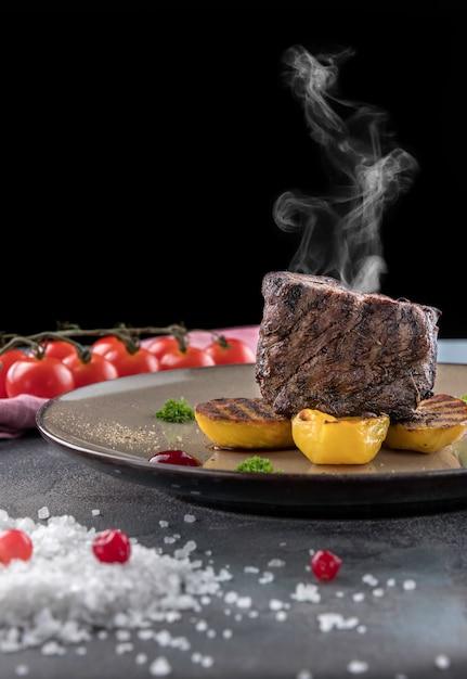 Steak filet mignon with smoke. baked potatoes, cranberry sauce, cherry tomatoes on a gray concrete background Premium Photo