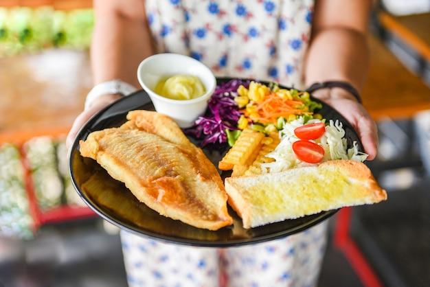 Стейк из рыбы с соусом, сливками, картофелем фри, хлебом и свежими овощами на тарелке Premium Фотографии