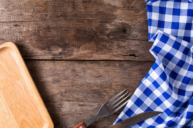 Steak knife and a fork with blue table cloth on wooden background Premium Photo