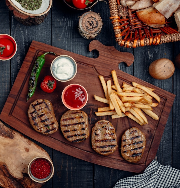 Steak pieces with french fries, grilled pepper and tomato, and sauces on a wooden board. Free Photo