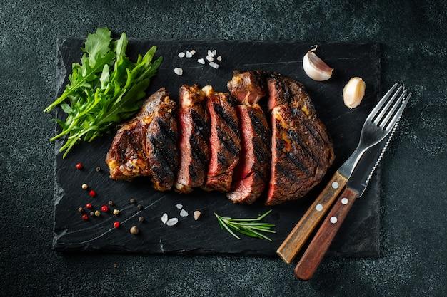 Steak ribeye, grilled with pepper and garlic. Premium Photo