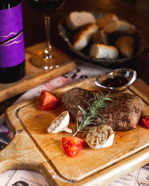 Steak served with grilled garlic, slices of tomato, rosemary sprig and sauce Free Photo
