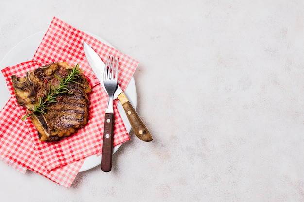 Steak with bone on plate Free Photo