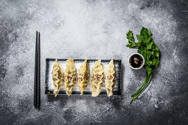 Steamed dim sum on a ceramic plate. gray background. top view. space for text. Premium Photo