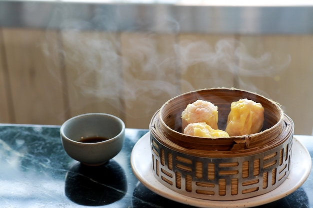 Steamed dumpling shrimp dim sum in bamboo steamer with smoke and sauce in the cups Premium Photo