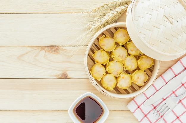 Steamed dumplings (chinese dim sum) in bamboo basket, serve with chopsticks on wooden tabl Premium Photo