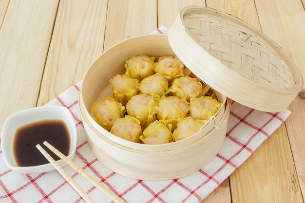 Steamed dumplings (chinese dim sum) in bamboo basket on wooden table background Premium Photo