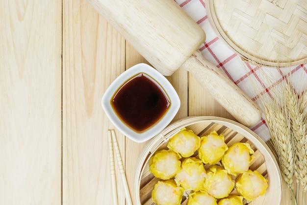 木製のテーブルの背景に竹のバスケットで蒸し餃子(中国のダムサム) Premium写真