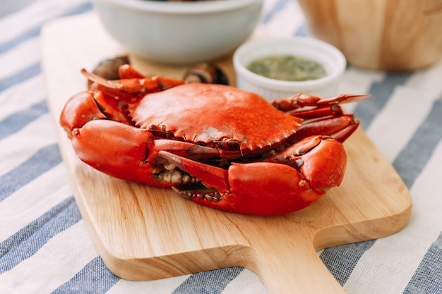 Steamed giant mud crab on wooden chopping board served with thai spicy seafood sauce and grilled laevistrombus canarium in shell in the background. Premium Photo