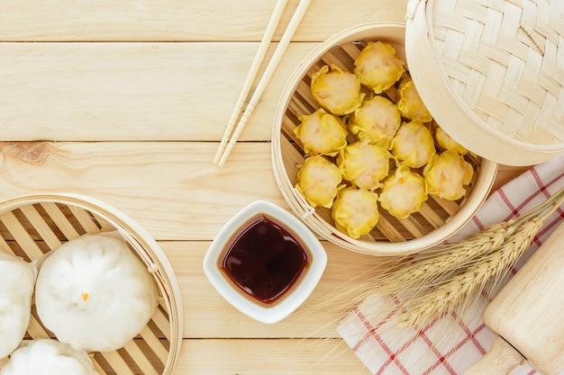 木製のテーブル上の竹のバスケットで蒸し豚のパン(中国のダムサム) Premium写真