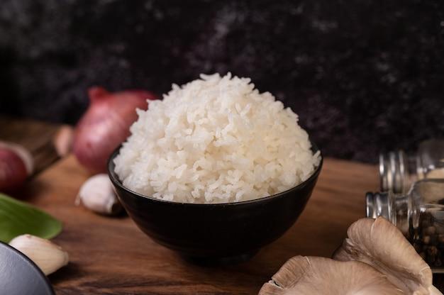 나무 커팅 보드에 마늘과 붉은 양파와 함께 그릇에 찐 쌀 무료 사진