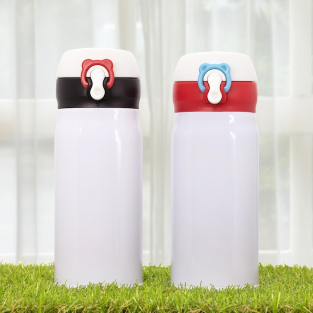 Steel bottle on curtains backdrops. insulated drink container. Premium Photo