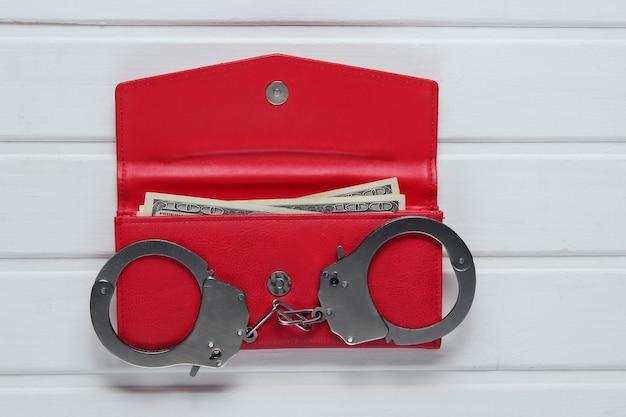 白いテーブルに赤い革の財布と鋼の手錠。盗難、犯罪の概念。 Premium写真
