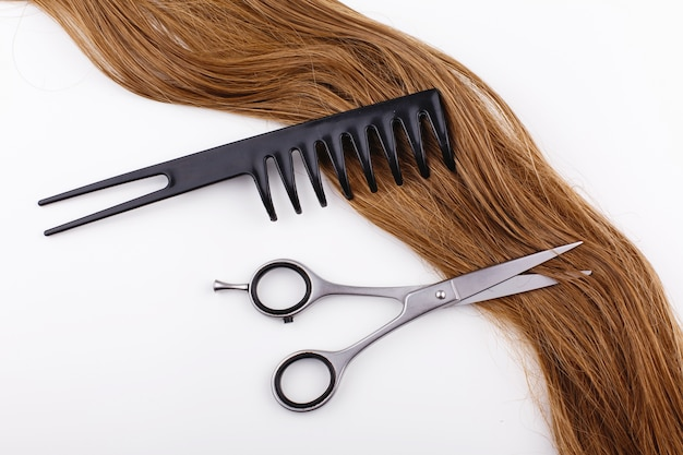 Steel scissors lie on the wave of silk brown hair with a black comb Free Photo