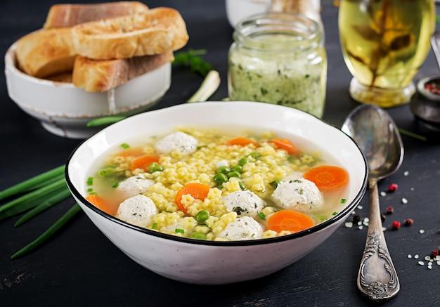Итальянский фрикадельки суп и stelline глютен макароны в миску на черном столе. диетический суп. детское меню. вкусная еда. Бесплатные Фотографии