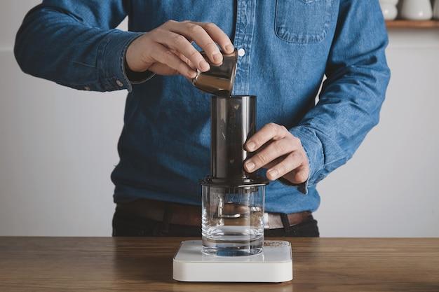 Пошаговое приготовление кофе в аэропрессе бариста в синей джинсовой рубашке переливает молотый кофе из стальной чашки в аэропресс профессиональное заваривание кофе кафе Бесплатные Фотографии
