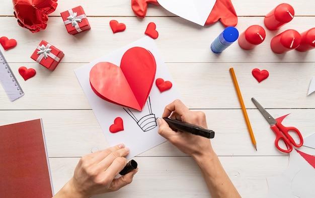 Пошаговая инструкция по изготовлению воздушного шара в форме сердца из бумаги. шаг 7 - используйте маркер или ручку, чтобы нарисовать корзину для воздушного шара Premium Фотографии
