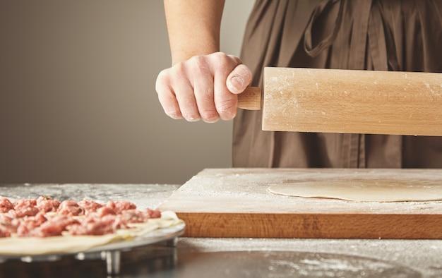 Processo graduale per preparare gnocchi, ravioli o pelmeni fatti in casa con ripieno di carne macinata utilizzando lo stampo per ravioli o la macchina per ravioli. isolato sul lato destro. appiattire la pasta con il mattarello Foto Gratuite