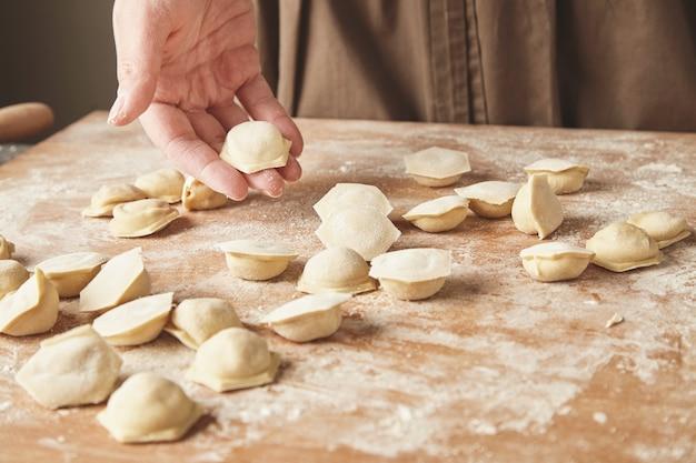 집에서 만든 만두, 라비올리 또는 라비올리 몰드 또는 라비올리 메이커를 사용하여 다진 고기로 채우는 펠 메니를 만드는 단계별 과정. 나무 보드에 라비올리 요리 준비, 여자 손 하나 보유 무료 사진