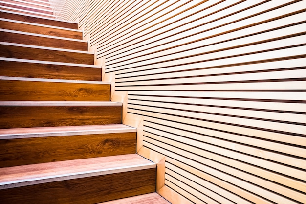 Steps on a ladder next to a wall of wooden boards in sustainable construction. Premium Photo
