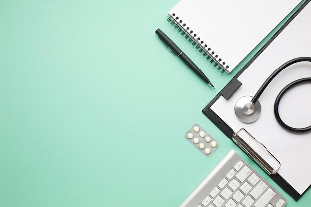 緑の背景の上のオフィス用品と聴診器と錠剤のブリスターパック 無料写真