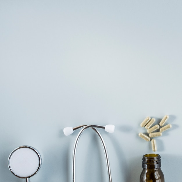 Stethoscope and capsules above the bottle over the grey background Free Photo