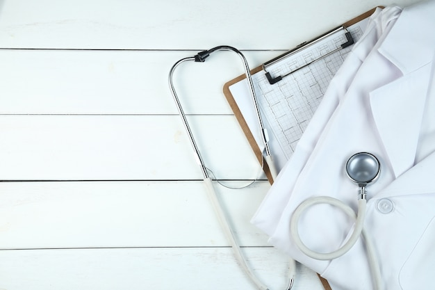 Stethoscope,clipboard and doctor's uniform on white neat wooden desk Free Photo