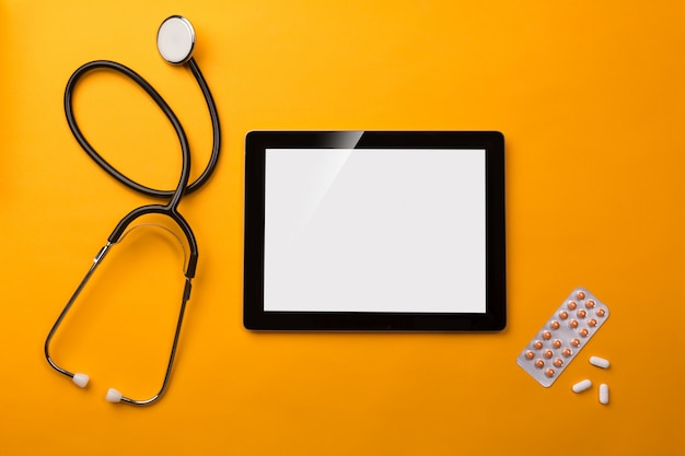 Stethoscope in doctors desk with digital tablet and pills Premium Photo