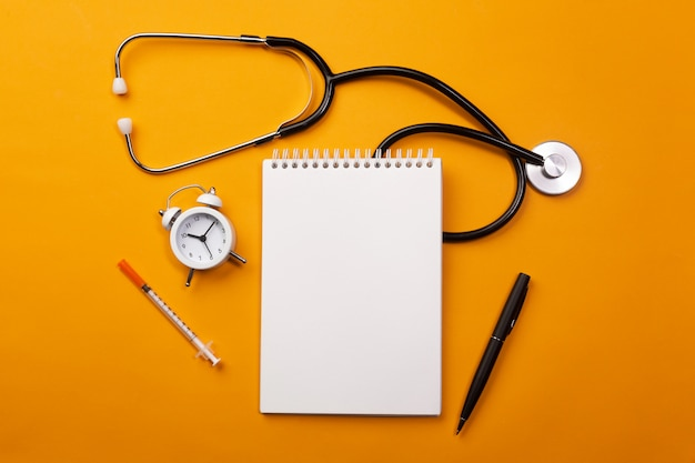 Stethoscope in doctors desk with notebook, alarm clock and pills Premium Photo