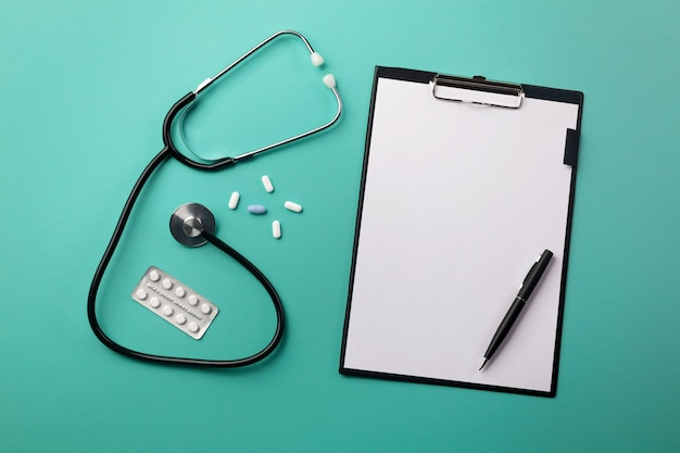 Stethoscope in doctors desk with tablet, pen and pills Premium Photo