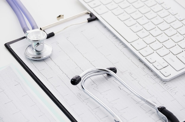 Stethoscope on ecg paper graph and laptop on white backdrop Free Photo
