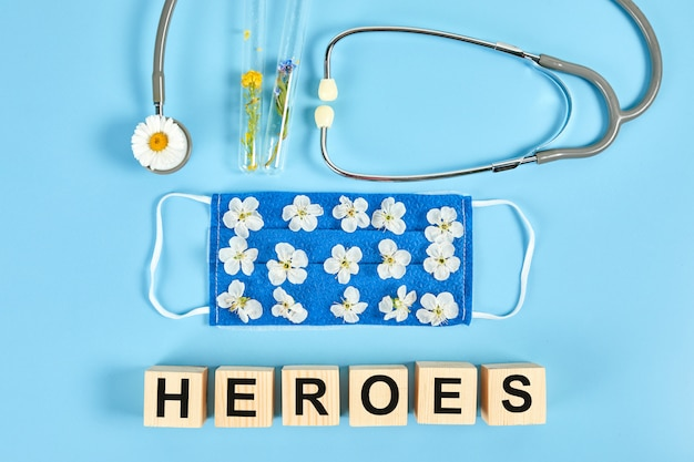 Stethoscope, flowers and medical protective mask with wooden cubes. text heroes, gratitude to medical personnel and doctors Premium Photo