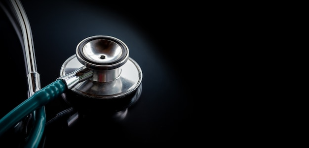 Stethoscope on a glass table, dark background, the concept of medicine and medical treatment Premium Photo