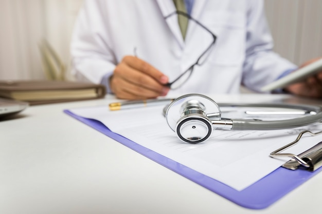 Stethoscope is lying on the clipboard near a doctor consults patient. Premium Photo