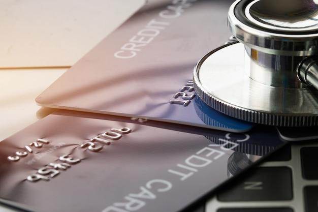 Stethoscope on mock up credit card with cardholder in hospital desk Premium Photo