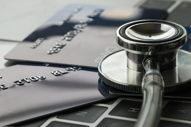 Stethoscope on mock up credit card with number on card at computer Premium Photo