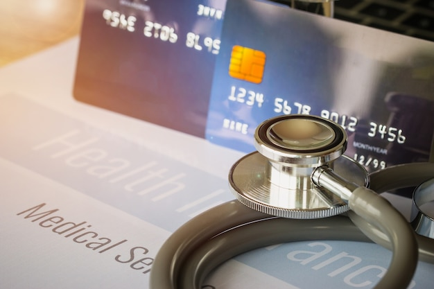 Stethoscope on mock up credit card with number on cardholder in hospital desk. health insu Premium Photo