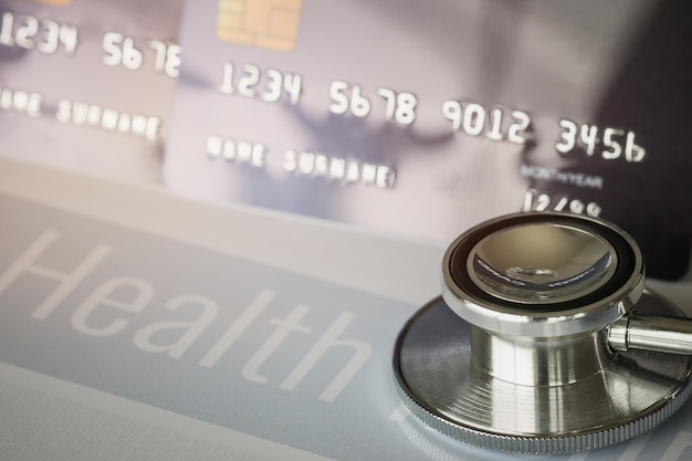 Stethoscope on mock up credit card with number on cardholder in hospital desk. health insurance Premium Photo