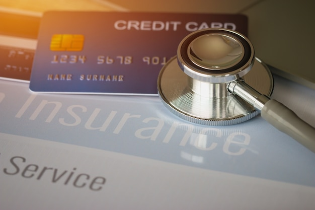 Stethoscope on mock up credit card with number on cardholder in hospital office Premium Photo