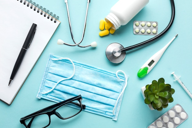 Stethoscope on notepad with medicines over blue backdrop Free Photo