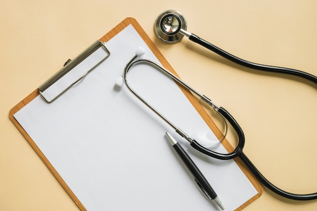 Stethoscope and pen over the clipboard with blank white paper on beige background Free Photo