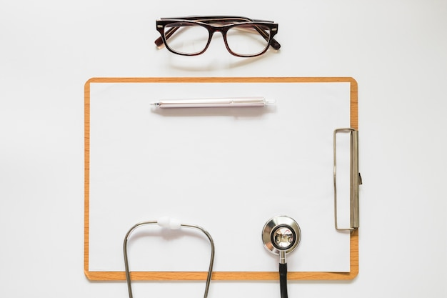 Stethoscope; pen and eyeglasses on clipboard with paper over the white background Free Photo