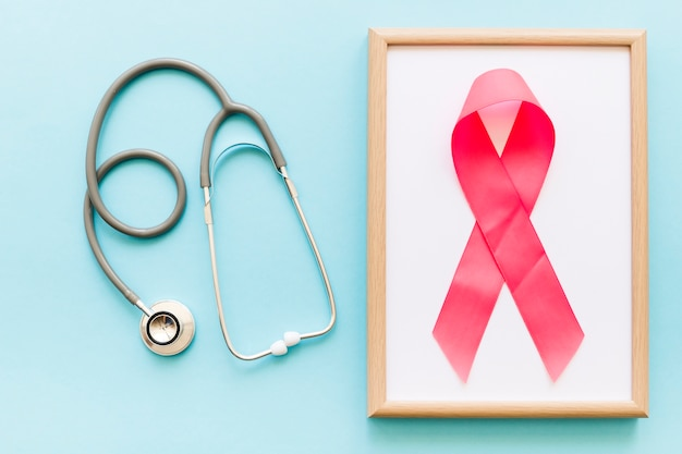 Stethoscope and pink ribbon on white wooden frame over the colored background Free Photo