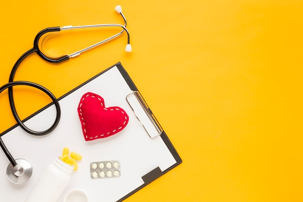 Stethoscope; stitched heart; medicine falling from bottles; blister packed medicine with clipboard over yellow table Free Photo