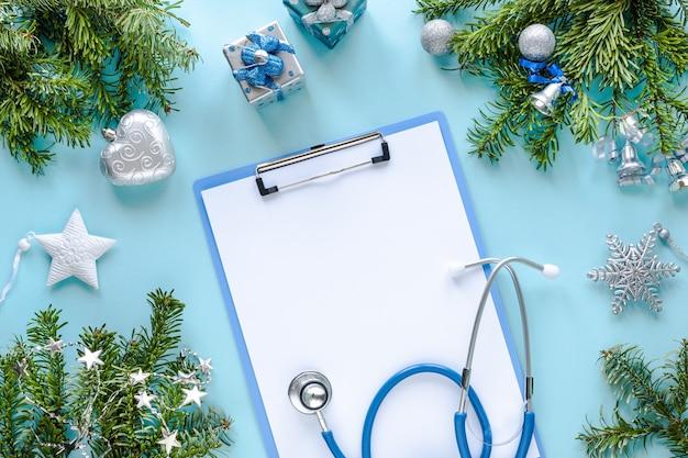 Стетоскоп, термометр, пустой буфер обмена и рождественские украшения Бесплатные Фотографии