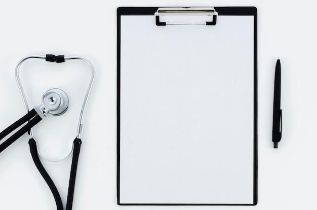 Stethoscope; white paper on clipboard with pen isolated on white backdrop Free Photo