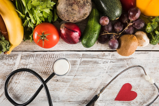 Stethoscope with heart shape near fresh vegetables on wooden background Free Photo