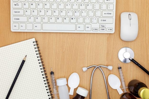 キーボード、マウス、ノート、鉛筆、ホワイトペーパー、木製の背景に薬物と聴診器。 Premium写真