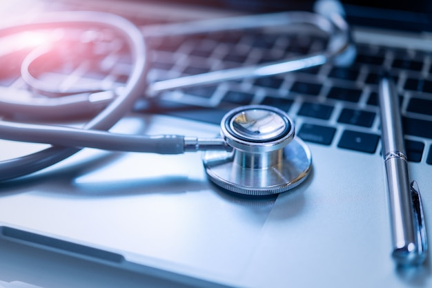 Stethoscope with pen on laptop,stethoscope for doctor check up on health medical laboratory. Premium Photo
