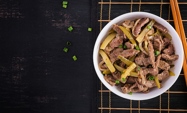 Stew beef, pieces of beef stewed in soy sauce with spices with pickled cucumber in asian style. top view, overhead, flat lay Free Photo